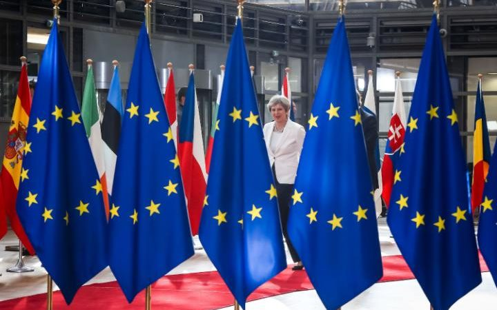 Britain's Prime Minister Theresa May walks behind flags of Europe
