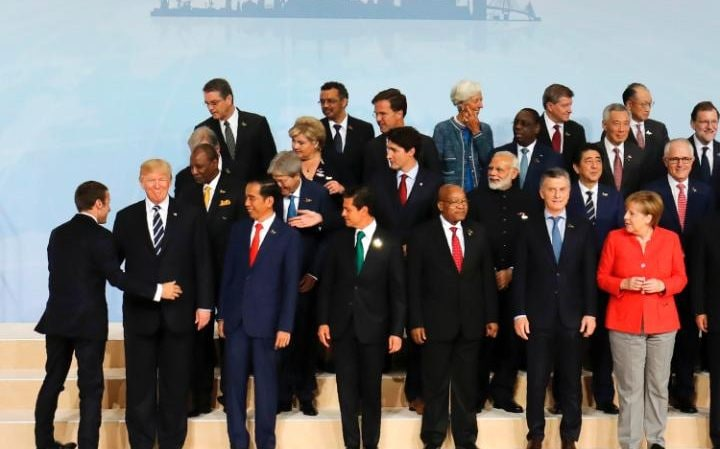 French President Emmanuel Macron (L) places himself next to US President Donald Trump (2ndL) after he left his position during the family picture as German Chancellor Angela Merkel (R) watches on