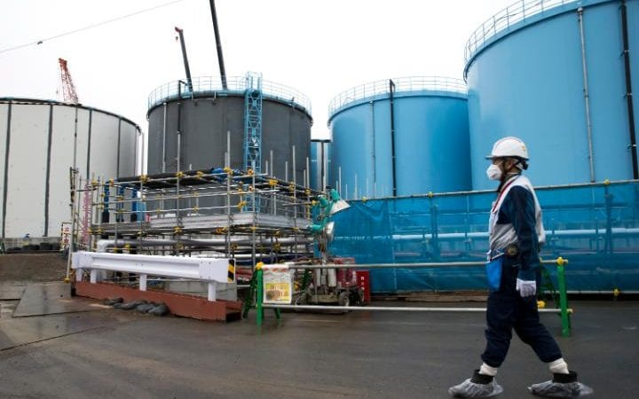 An employee walks past storage tanks for contaminated water at the tsunami-crippled Fukushima Dai-ichi nuclear power plant