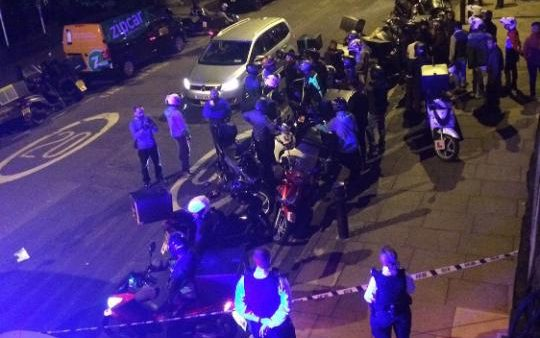 Drivers at the scene along with police after two men on a moped carried out five acids attacks during a spree across the capital