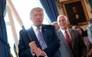 Vice President Mike Pence laughs as U.S. President Donald Trump holds a baseball bat as they attend a Made in America product showcase event