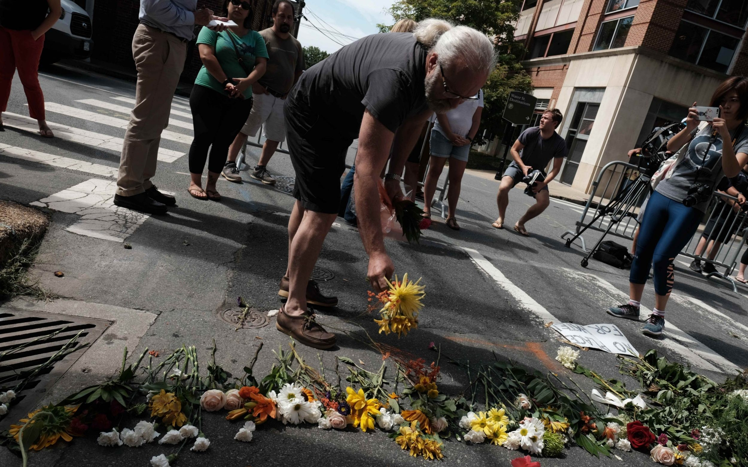A mourner lays flowers at a makeshift memorial at the scene of where a car plowed into counter-protesters in Charlottesville