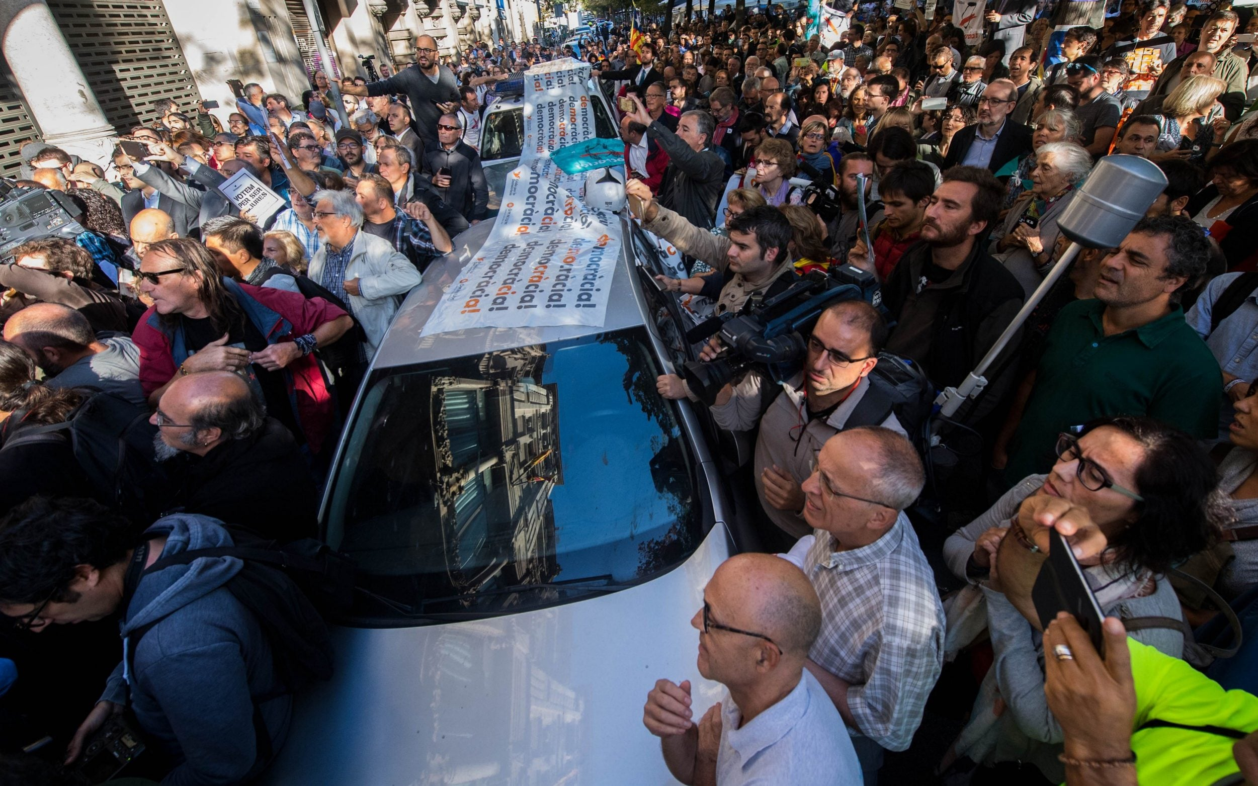 People surround Spanish Civil Guard Police cars outside the Catalan Vice-President and Economy office as police officers hold a searching operation inside on September 20