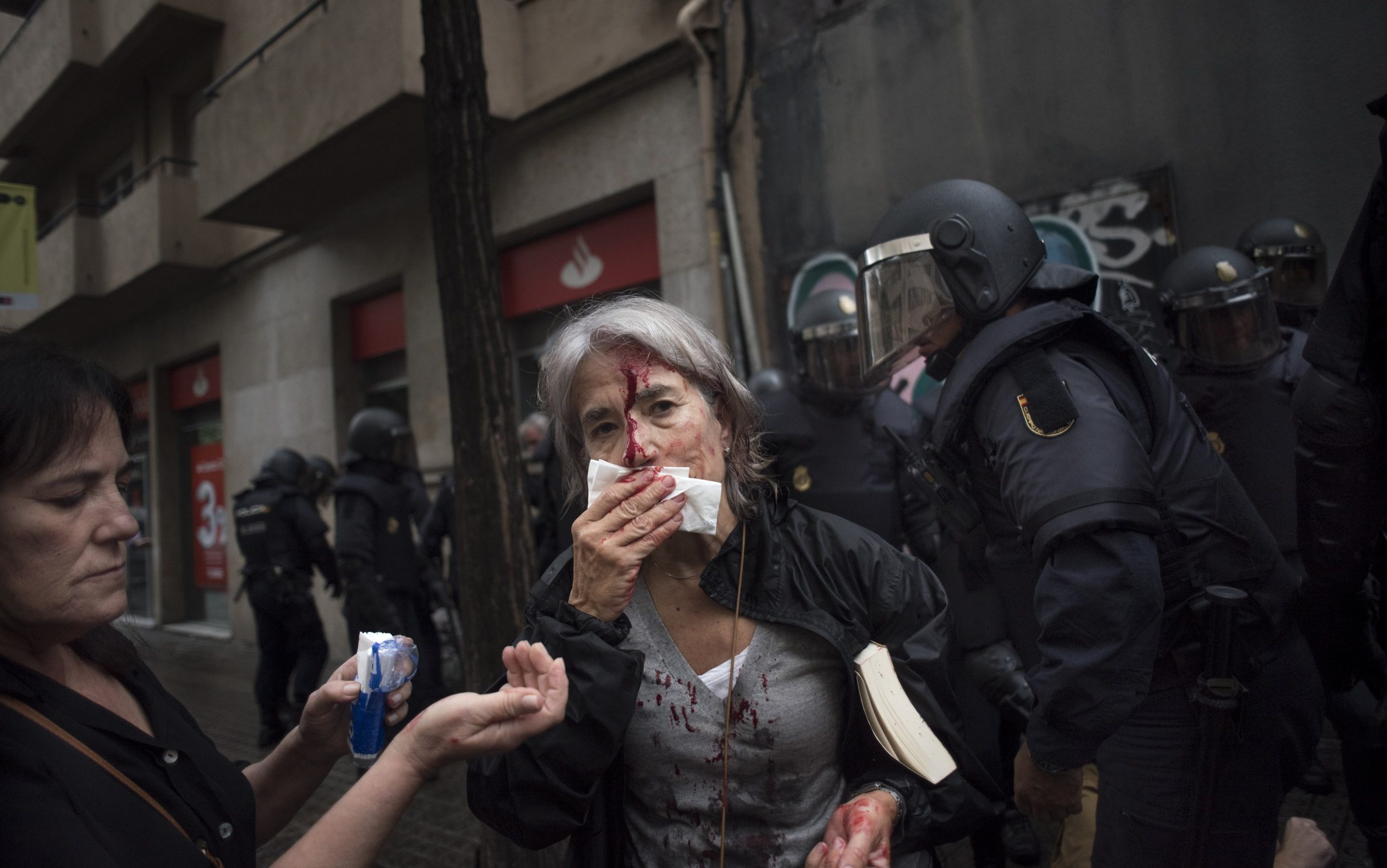 A woman tends to her injuries in front of riot police near a school being used as a polling station