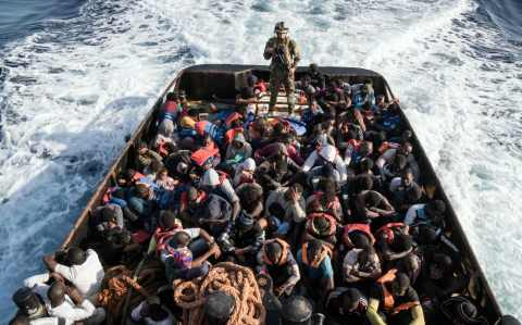 A Libyan coast guardsman stands on a boat during the rescue of 147 illegal immigrants attempting to reach Europe off the coastal town of Zawiyah, 45 kilometres west of the capital Tripoli, on June 27, 2017.