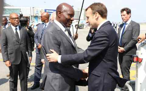 French President Emmanuel Macron (R) is welcomed by Ivorian Vice President Daniel Kablan Duncan (L) at Port Bouet Airport as he arrives to take part in the 5th African Union-European Union Summit in Abidjan, Ivory Coast