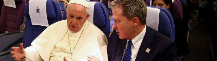 Pope Francis chats with Greg Burke, director of the Holy See Press Office, during a news conference on board the plane during his flight back from a trip to Chile and Peru.