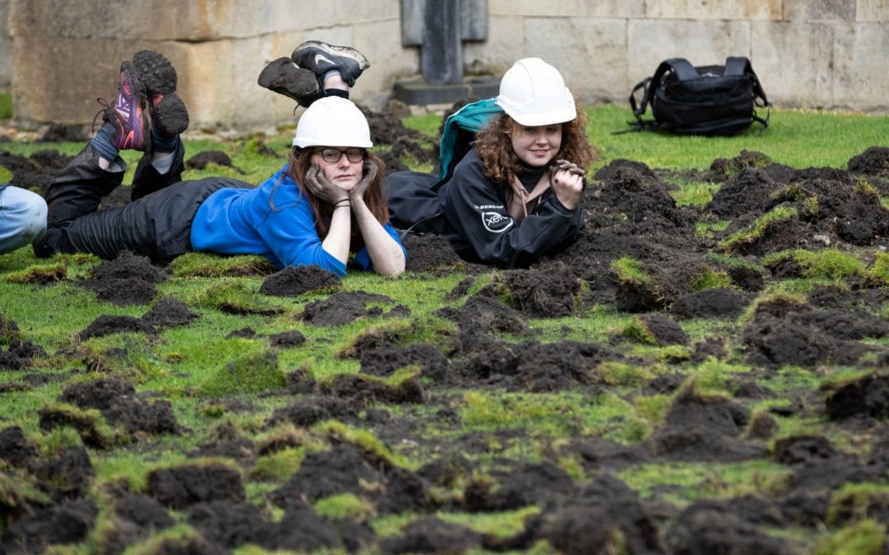 Climate change protesters dig up Trinity College lawn at Cambridge