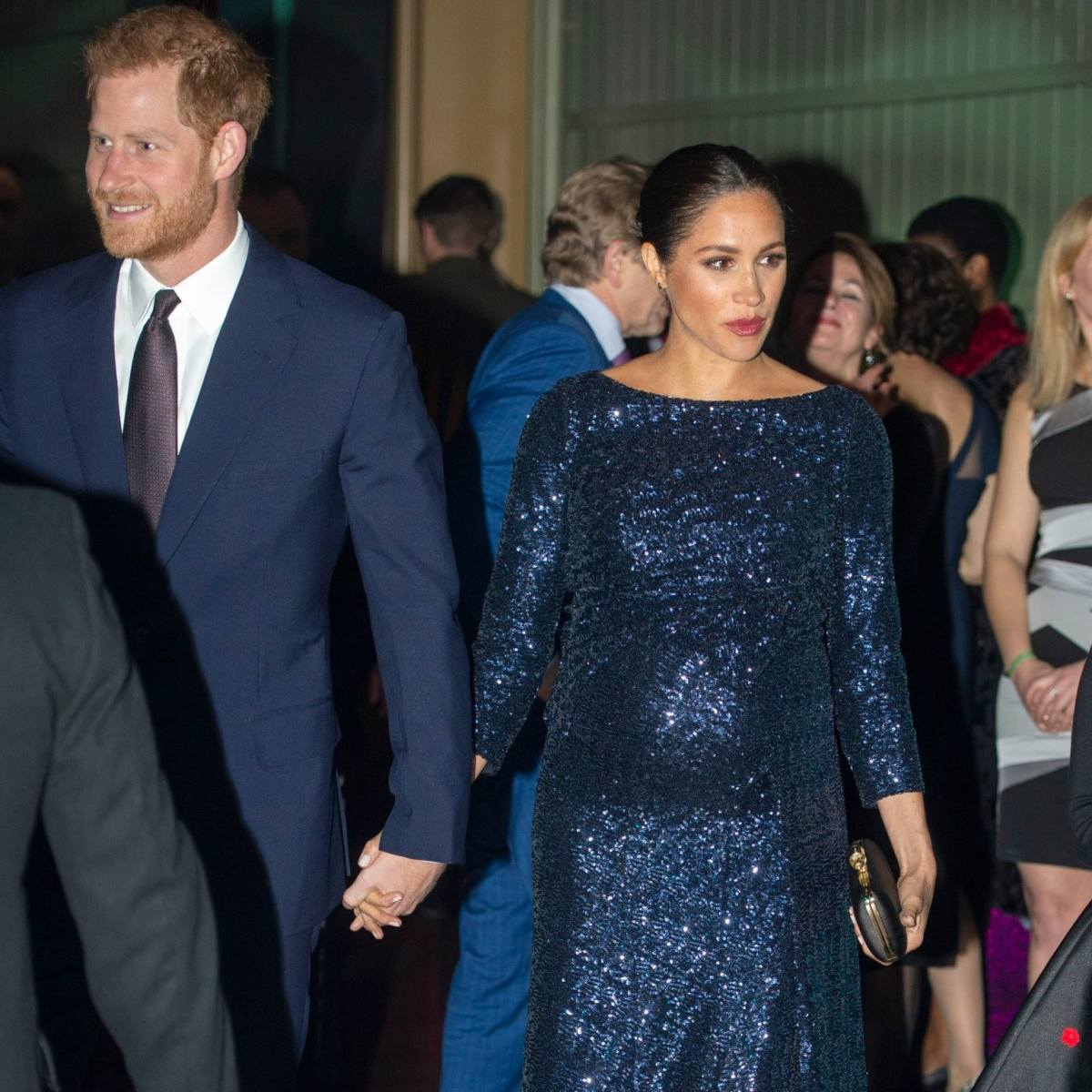 The Duke and Duchess of Sussex hold hands as they attend the event at the Royal Albert Hall