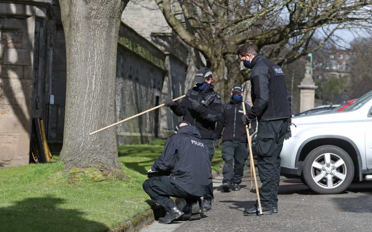 Police officers conduct a search outside the Palace of Holyroodhouse in Edinburgh