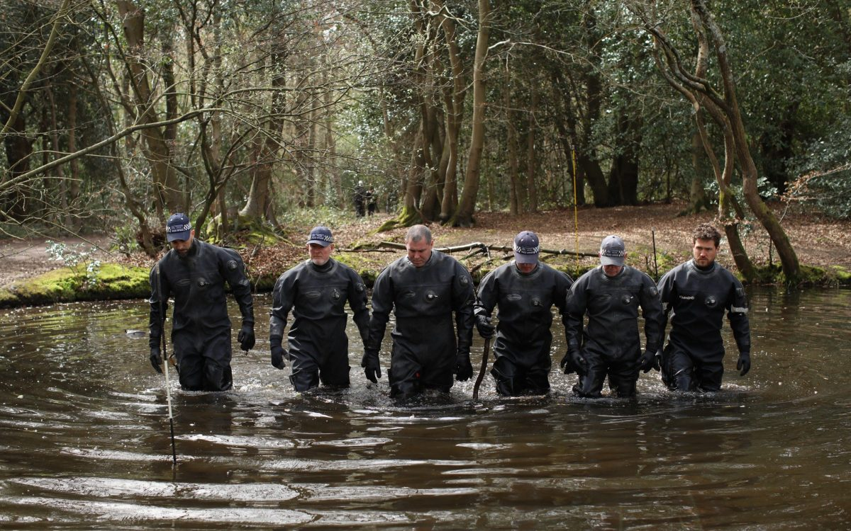 Police search teams search a pond in Epping Forest