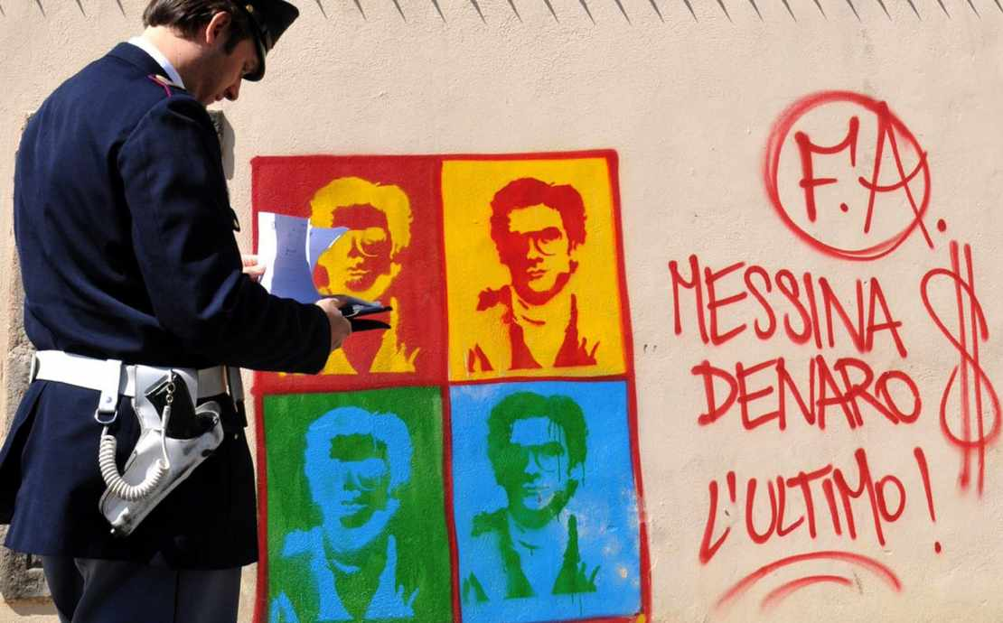 An Italian Police officer in Palermo, Sicily, looks on at graffiti on the perimeter wall of the city's cathedral, portraying Matteo Messina Denaro, a fugitive Mafia boss from the city of Trapani, in western Sicily