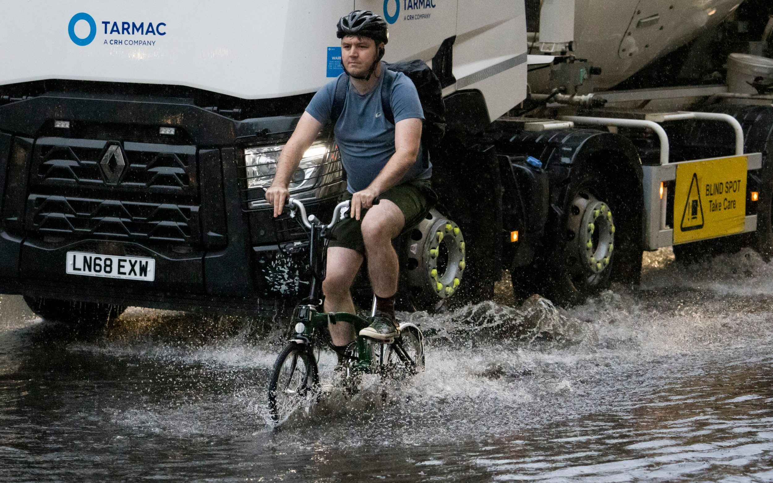 A cyclist ploughs through surface water on Euston road