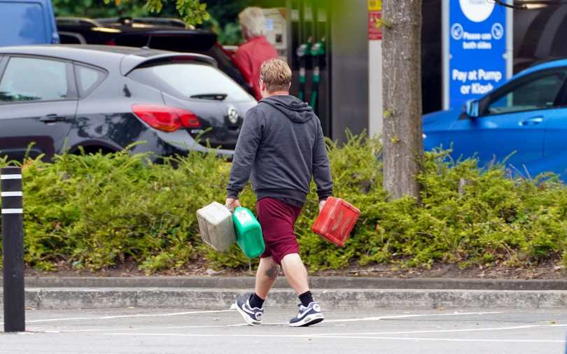 A man carrying jerry cans at a Tesco Petrol Station in Bracknell, Berkshire