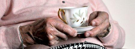 Elderly lady holding a mug of tea