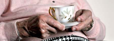 Elderly lady holding a mug of tea