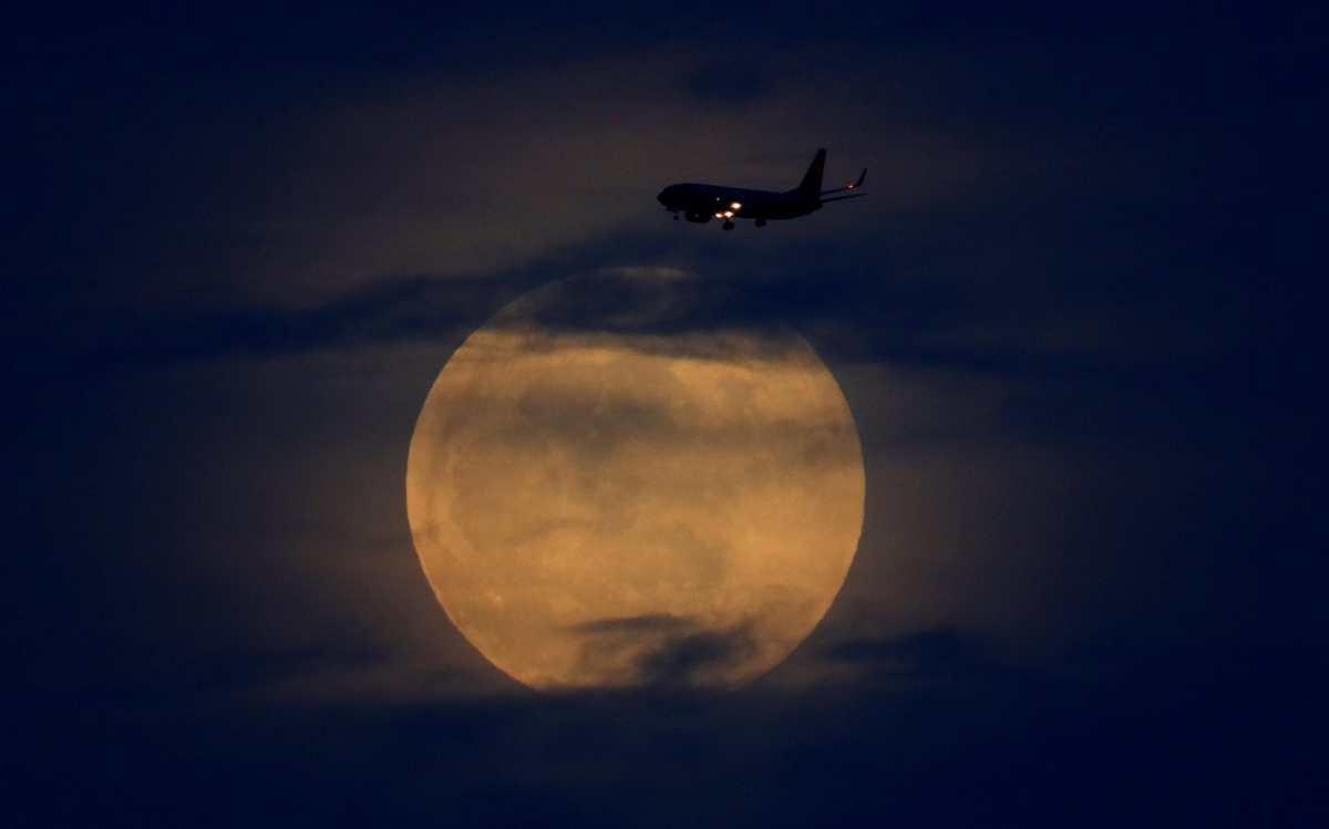 A plane passes as the moon rises through clouds before start of total lunar eclipse in California