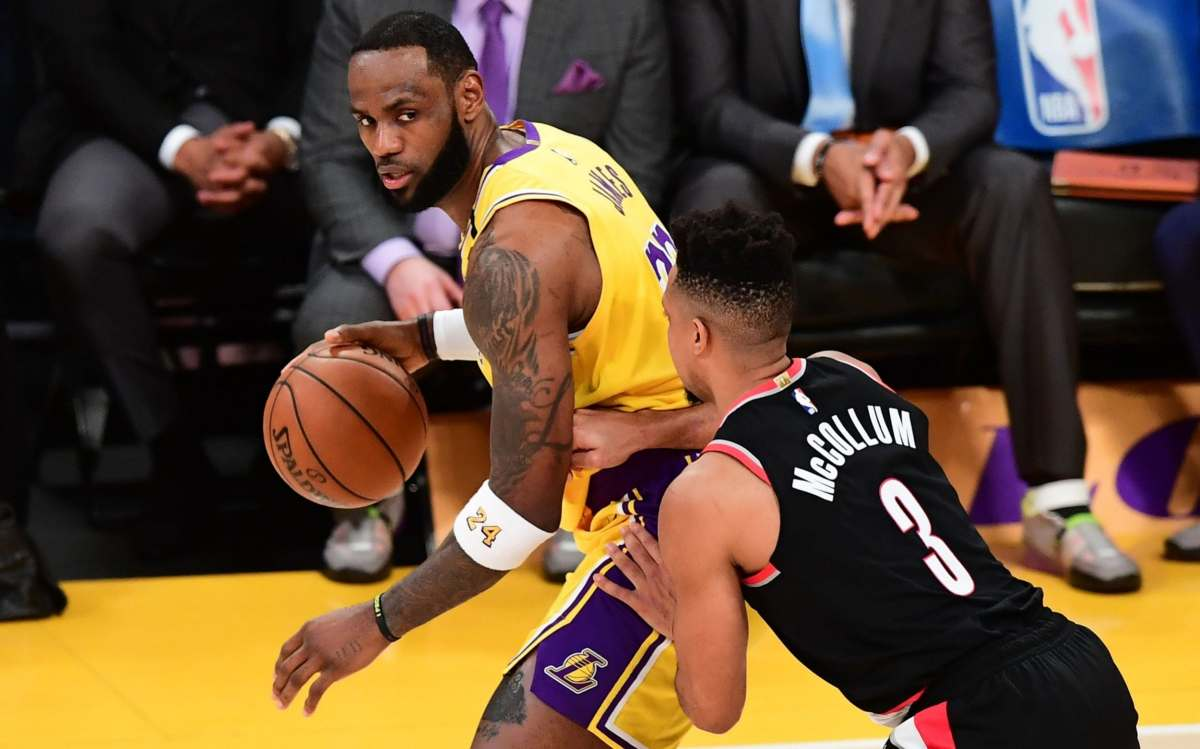 LeBron James of the Los Angeles Lakers looks to pass under pressure from CJ McCollum of the Portland Trailblazers
