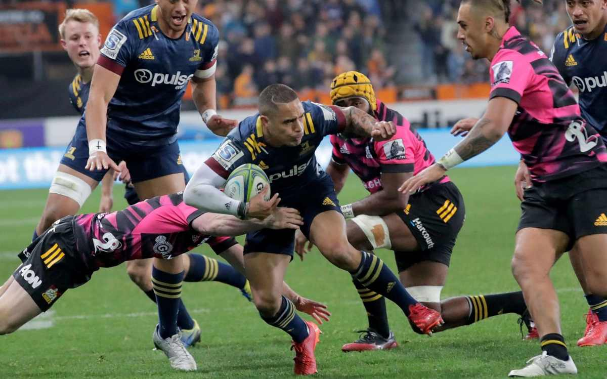 Highlanders' Aaron Smith (C) is tackled during the Super Rugby match between the Highlanders and Chiefs