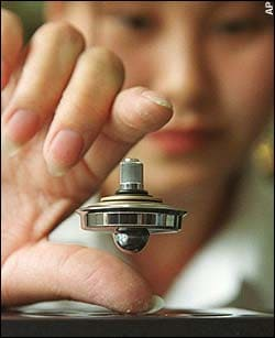Beijing saleswoman demonstrates toy which levitates by magnetic force; Physicists have 'solved' mystery of levitation