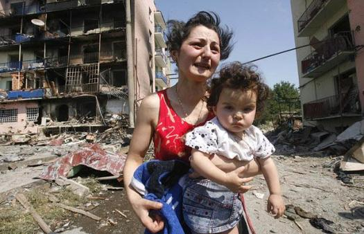 A distraught Georgian woman holding her baby outside an apartment block destroyed by Russian warplanes
