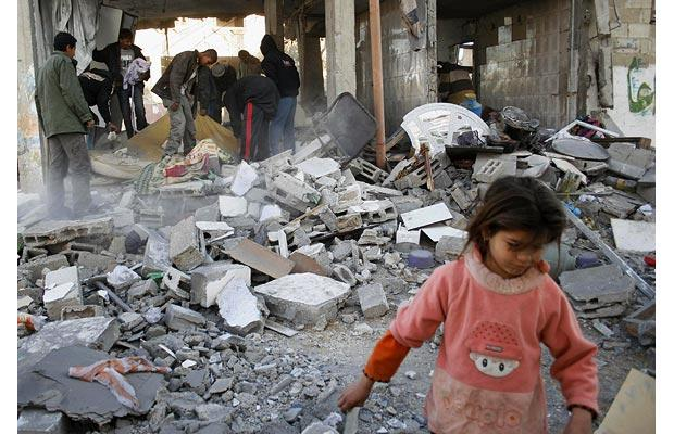 A Palestinian girl walks amid rubble as others remove their belongings from a destroyed building following Israeli military operations in Rafah, southern Gaza Strip