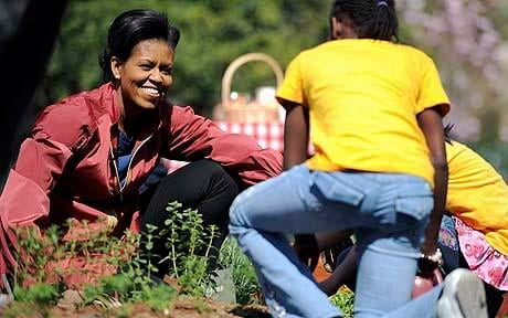 First lady Michelle Obama smiles as she helps students plant herbs in the White House Kitchen Garden.
