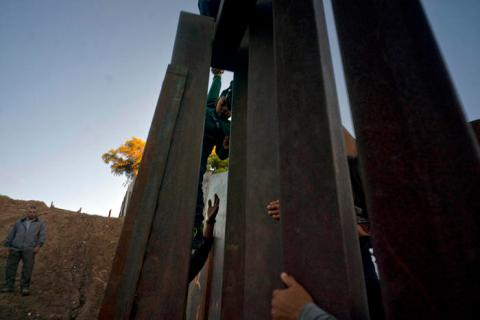 Migrants from Honduras cross the wall from Tijuana to the United States.