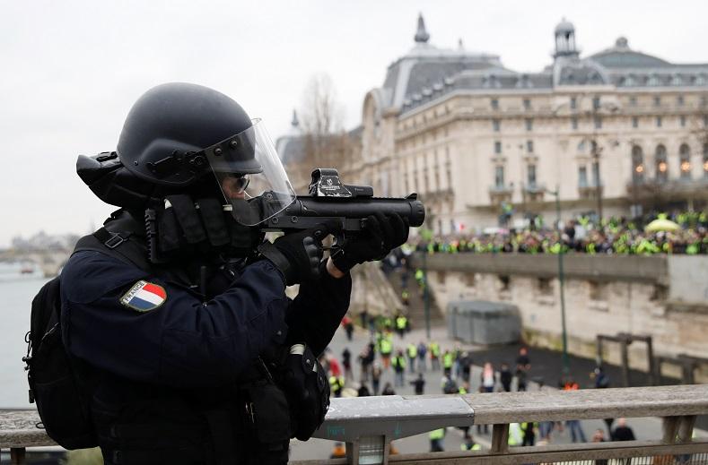 A policeman points a flash-ball gun at demonstrators in Paris.