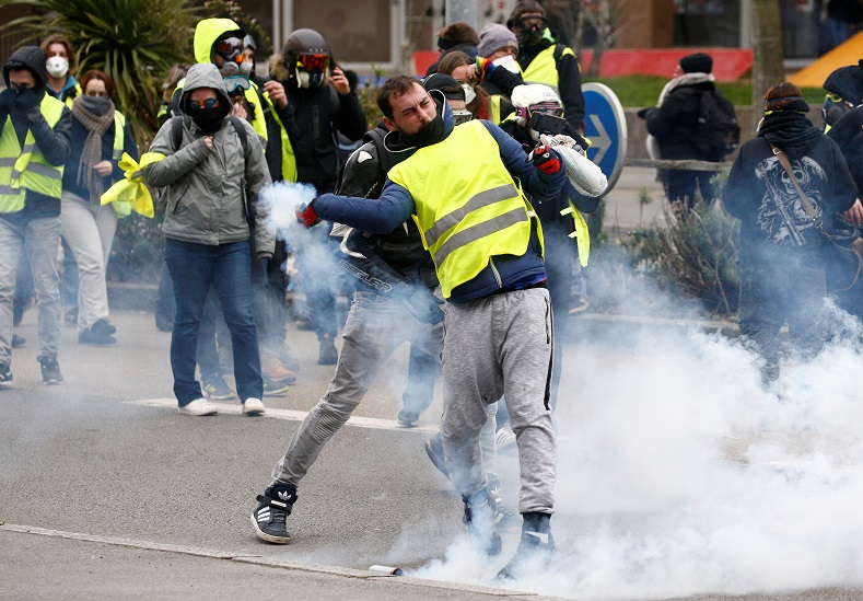 A protester throws tear gas canister back at police.