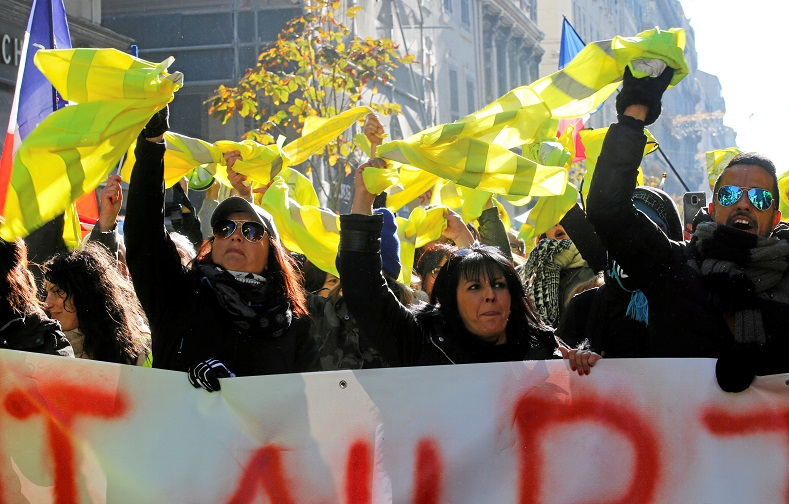 Protesters hold yellow vests as they take part in a demonstration in Marseille.