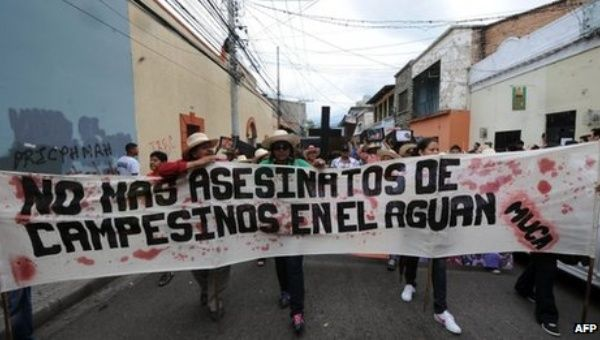 """Resistance group Movimiento Unificado Campesino del Aguan (Unified Campesino Movement of the Aguan) holds a sign that says """"No more murders of campesinos in the Aguan."""" (Photo: AFP)"""