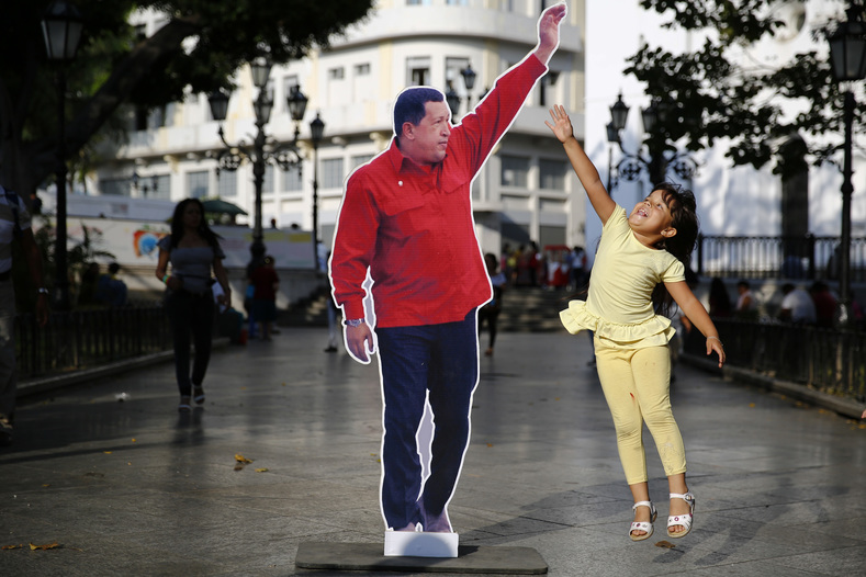 Girl plays with a Chavez cardboard figure in Plaza Bolivar, Caracas. Plaza Bolivar, which connects with the Venezuelan national assembly, is site of numerous spontaneous political activities and events.