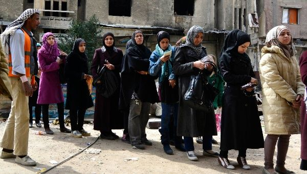 Residents line up to receive humanitarian aid at the Palestinian refugee camp of Yarmouk, in Damascus, March 11, 2015.