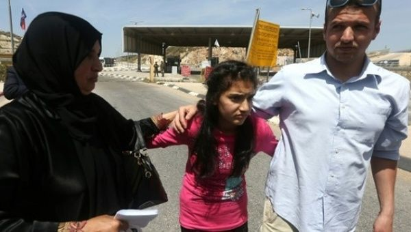The mother and brother of Palestinian Dima al-Wawi, 12, who was the youngest female detained in Israel, greet her in the West Bank city of Tulkarem, April 24, 2016.