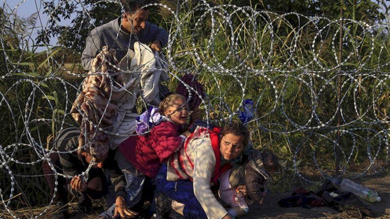 Refugiados sirios cruzan una cerca para entrar a Hungría en la frontera con Serbia.