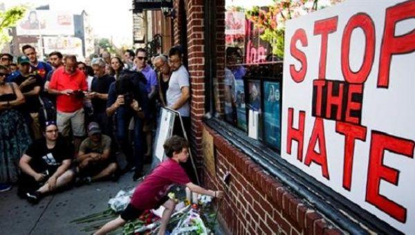 """El cartel dice """"alto al odio"""". Decenas de personas homenajearon a los muertos en el bar LBGTI llamado Pulse de Orlando."""