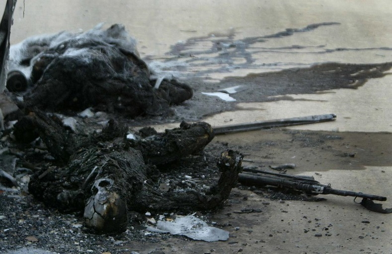 The charred remains of dead Iraqi soldiers lay outside a bus hit by a tank shell on a highway between Baghdad