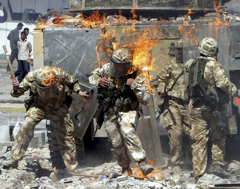 British troops are covered in flames from a gasoline bomb thrown during a violent protest in Basra, March 2004.