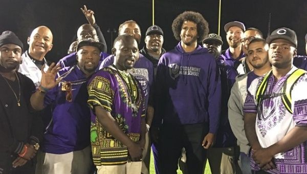 49ers quarterback Colin Kaepernick poses alongside players and coaches from Oakland's Castlemont High School, Sept. 23, 2016.