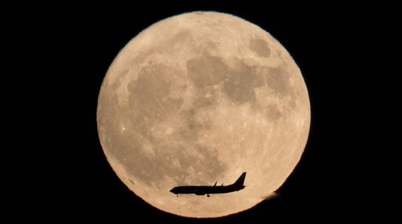 Un avión a través de la luna visto desde Beijing, China.