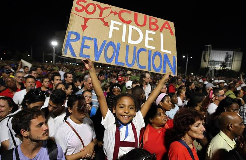 "A schoolgirl waves a sign reading ""I am Cuba and Fidel and Revolution."""