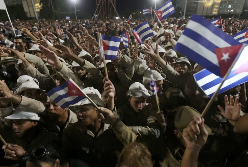 People wave Cuban flags as they attend a massive tribute to Cuba