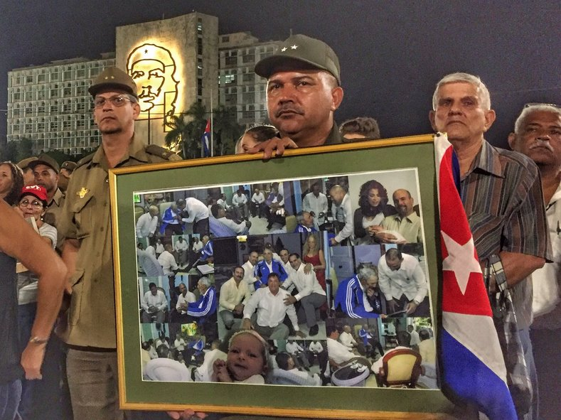 A mourner holds a photo tribute to Fidel Castro