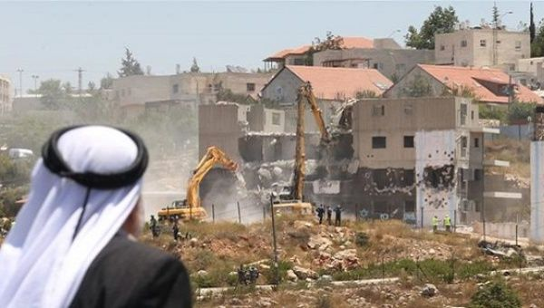 A Palestinian man watches Israeli heavy machinery demolish apartment blocs in the occupied West Bank settlement of Beit El, July 29, 2015.