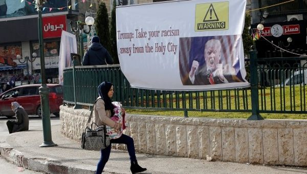 A Palestinian woman walks past a banner against U.S. President Donald Trump