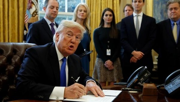 President Donald Trump looks up while signing an executive order to advance construction of the Keystone XL pipeline at the White House in Washington.