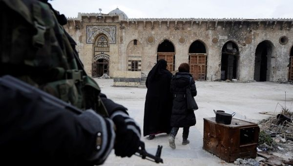 A Syrian Army soldier stands guard as visitors walk inside Aleppo