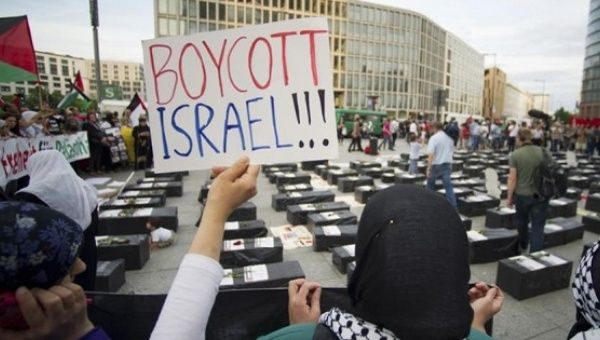 A woman holds a sign in front of symbolic coffins protesting the Israeli occupation.