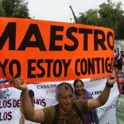 """A protester holds a sign reading, """"Teacher, I am with you!"""" as people demonstrate in support of the CNTE teachers"""
